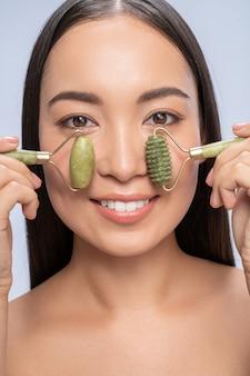 같이 해. 옥 롤러를 사용하여 피부를 관리하는 매력적인 국제 여성