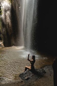 参加してください。カメラでポーズをとって、岩を見ながら半位置に座っているかわいいブルネットの女の子