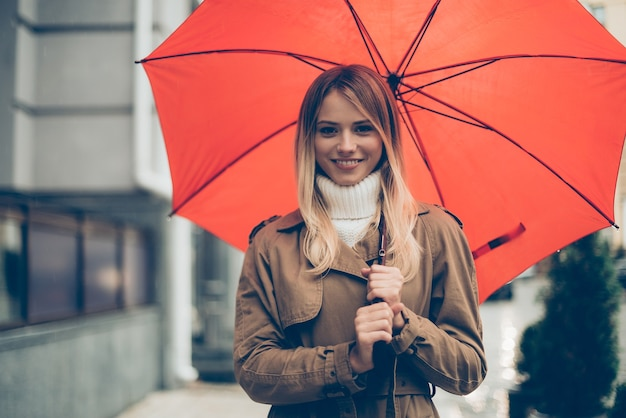 Join me under my umbrella! attractive young smiling woman carrying umbrella and looking at camera while standing on the street