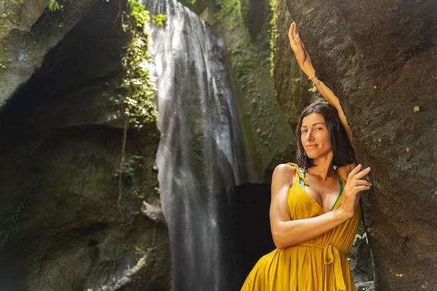 参加してください。前景の岩の近くに立って、彼女の顔に笑顔を保ちながら満足しているブルネットの女性