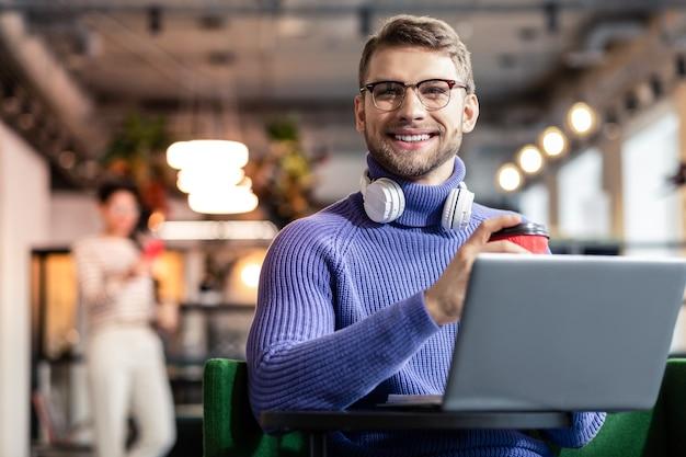 Присоединяйся ко мне. доволен молодой офисный работник, сидящий напротив компьютера во время перерыва