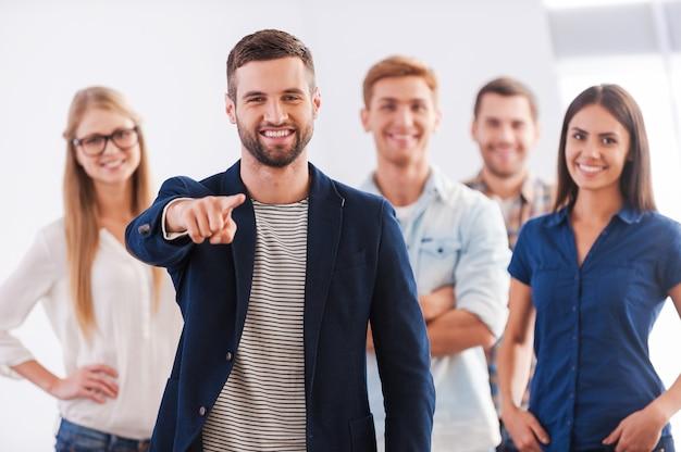 Присоединиться к нашей команде! красивая молодая женщина показывает палец вверх и улыбается, в то время как группа счастливых молодых людей стоит на фоне и улыбается