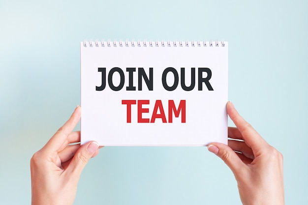 Join our team word inscription on white paper sheet in hands of a woman.