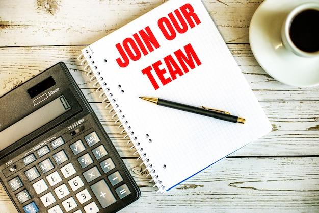 軽い木製のテーブルの上のコーヒーと電卓の近くの白い紙に書かれた私たちのチームに参加してください。ビジネスコンセプト