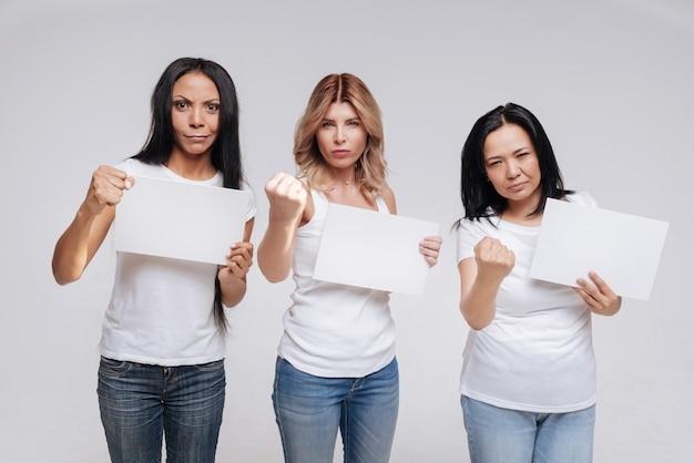 Присоединяйтесь к нам в нашей борьбе. великолепные уверенные в себе решительные дамы делают вид, что вместе протестуют против чего-то и сжимают кулаки