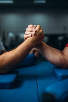 テーブル、レスリングのコンセプトで男性の手に参加しました