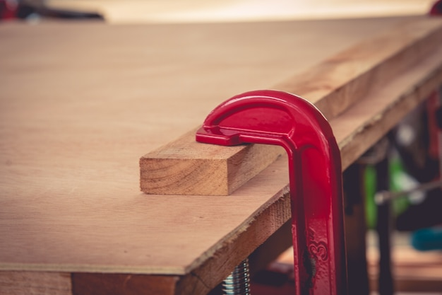 Joiner fastens clamps on a wooden surface for better gluing.