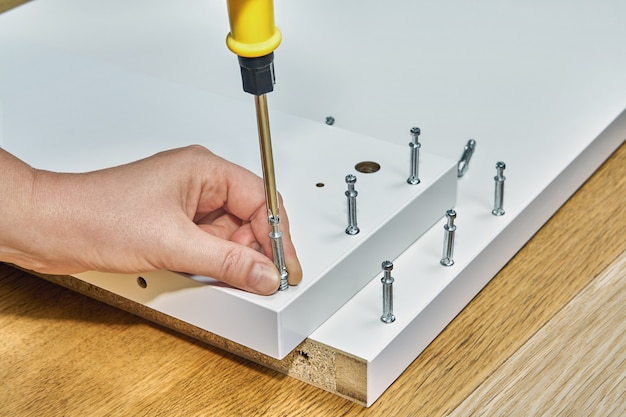 Joiner is screwing locking screws of flat pack during furniture assembly.