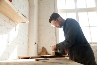Joiner polishes wooden board in workshop