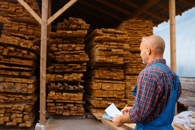 Joiner in uniform check boards on timber mill, lumber industry, carpentry. wood processing on factory, forest sawing in lumberyard, warehouse outdoor