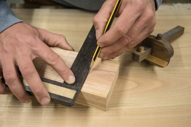 A joiner with a pencil and a square marks the workpiece