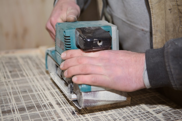Joiner working with a manual electric sander on the desktop in production