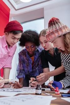 ガールフレンドに参加します。帽子をかぶった2人のハンサムな男子生徒が魅力的なガールフレンドに加わりました