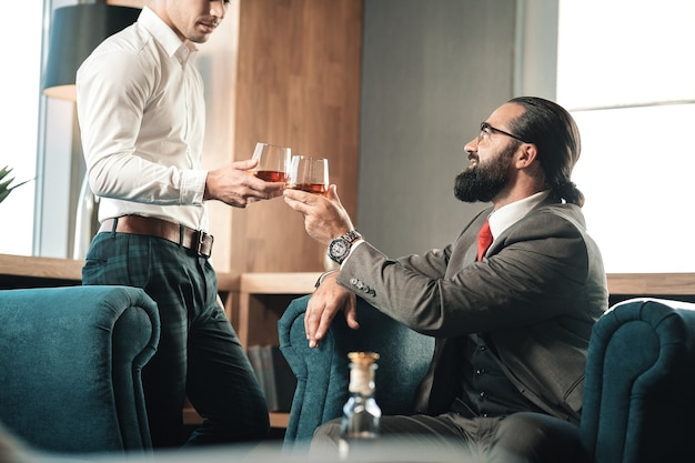 Присоединяйтесь к своему боссу. молодой красивый стильный сотрудник присоединяется к своему боссу в ресторане, пьющем виски