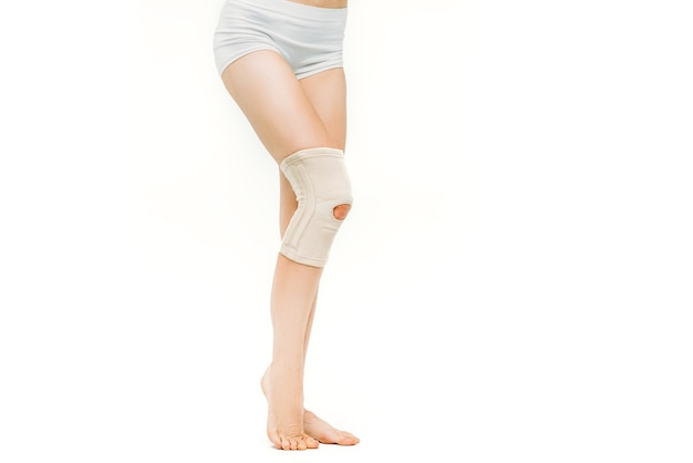Joint ache, woman with elastic bandage, knee pain on white.