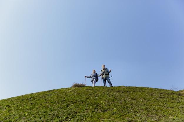 Совместные достижения. возрасте семейная пара мужчина и женщина в туристическом снаряжении, идущем на зеленой лужайке рядом с деревьями в солнечный день. концепция туризма, здорового образа жизни, релаксации и единения.