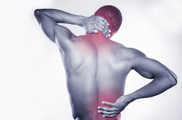 Боль в суставах. вид сзади молодого мускулистого африканского мужчины, касающегося его шеи и бедра, стоя на сером фоне