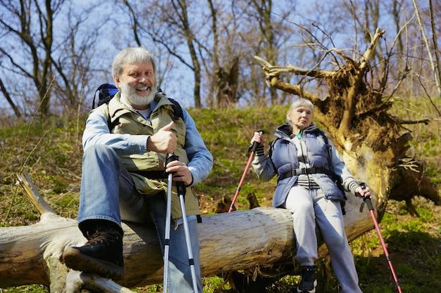 Совместный отдых вдвоем. возрасте семейная пара мужчина и женщина в туристическом снаряжении, идущем на зеленой лужайке рядом с деревьями в солнечный день. концепция туризма, здорового образа жизни, релаксации и единения.
