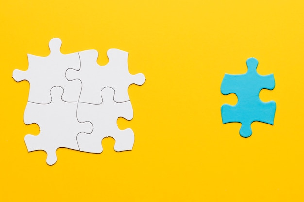 Joint white puzzle with a blue single piece on yellow surface