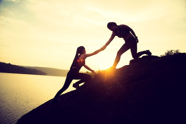 The joint work teamwork of two people girl sport  help each other on top of a mountain cli