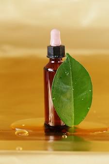 금 병에 갈색 병에 녹색 잎 호호바 오일