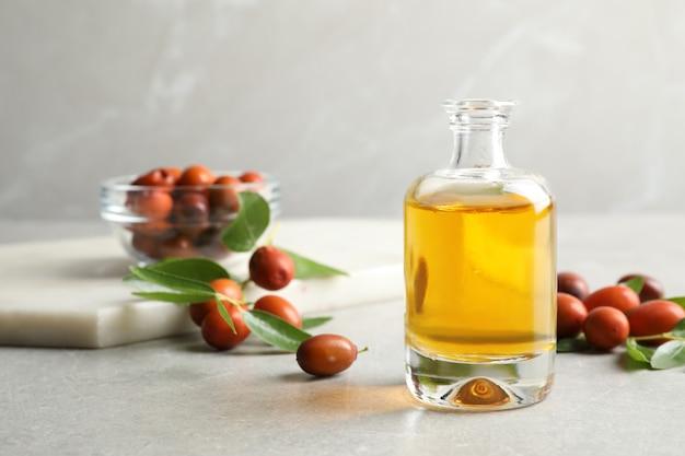 Масло жожоба в стеклянной бутылке и семена на светло-сером столе