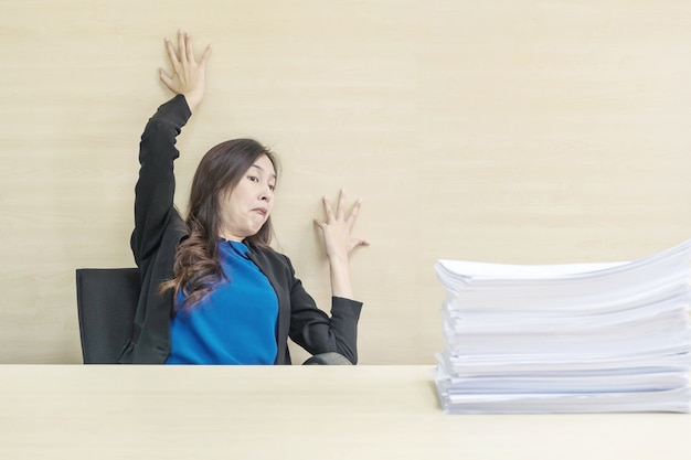 Joke action of working woman are afraid pile of work paper in front of her