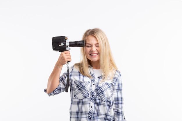 Шутка, фото и концепция жестов - молодая смешная глупая женщина позирует с камерой возле его головы.