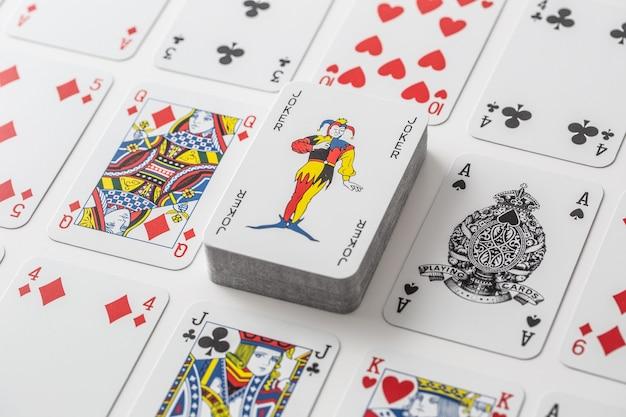 他のさまざまなトランプに囲まれたカードの山に乗ったジョーカー。