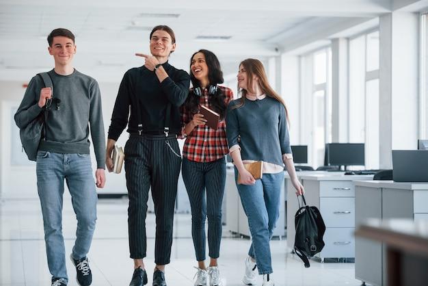 Шутят. группа молодых людей, идущих в офисе во время перерыва