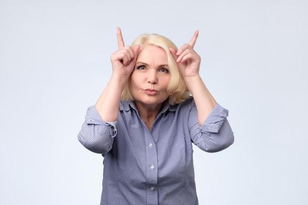 角のジェスチャーを示す冗談シニアブロンドの女性