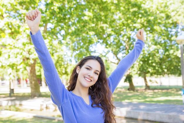 Jolly beautiful woman stretching outdoors