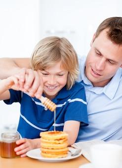 ジョリー少年と父親がワッフルに蜂蜜を入れている