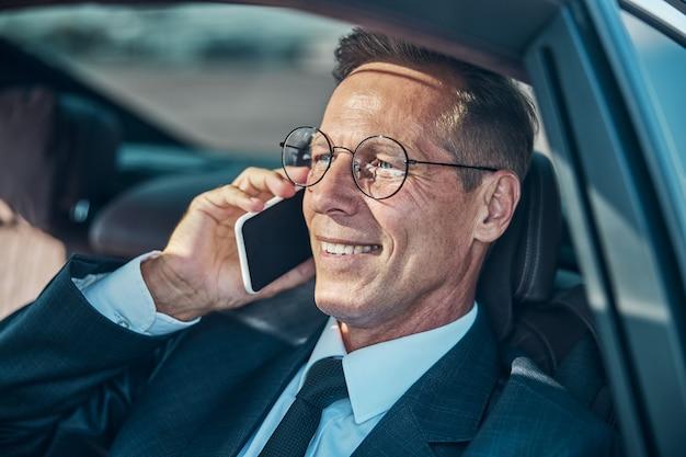 エレガントなスーツと眼鏡をかけた陽気なビジネスマンは、輸送中に座って携帯電話でチャットしています