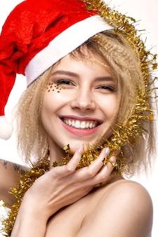 Веселая жизнерадостная красивая девушка в новогоднем образе с праздничным макияжем, одетая в деда мороза с улыбкой. красота лица. фотографии сняты в студии.