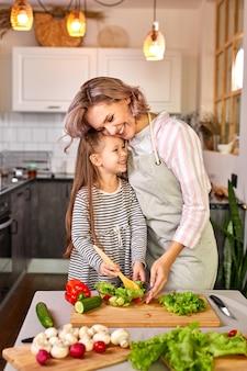 Веселая девочка готовит салат со своей мамой на современной светлой кухне, наслаждается процессом приготовления еды