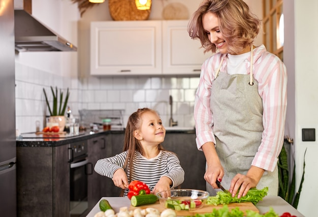 Jolly child girl preparing a salad with her mother in the modern light kitchen, enjoy the process of preparing meal