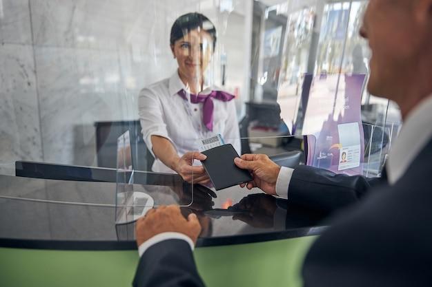 유쾌한 우아한 남성이 공항 등록 지점에서 웃는 여성에게 문서와 티켓을 주고 있다