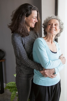 Jolly excited senior woman hugged by daughter turning back