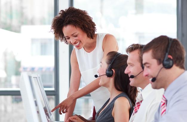 Веселая женщина-менеджер с ее представительной командой по продажам