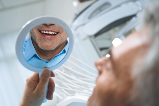 Jolly man is looking at mirror and enjoying reflectiong of his smile after dental procedures.