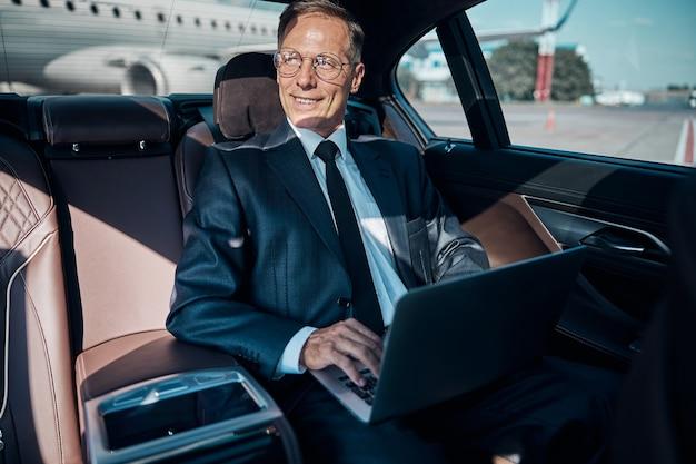 Веселый зрелый элегантный мужчина использует ноутбук, пока водитель несет его после прибытия из поездки