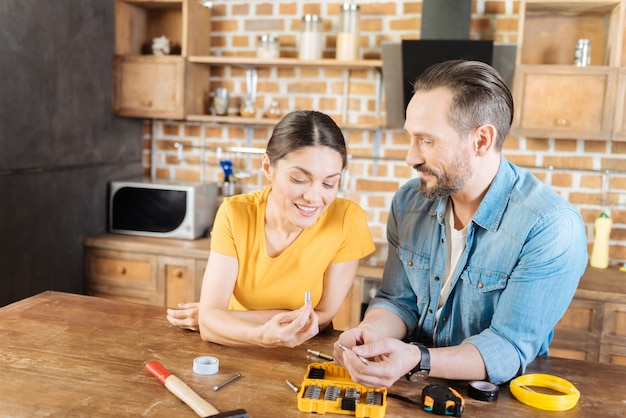 Jolly merry nice couple examining nails while smiling and discussing right choice