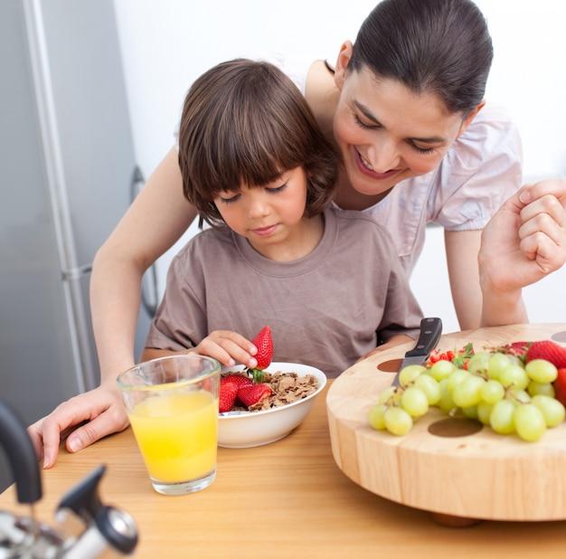유쾌한 어머니와 그녀의 아이가 아침을 먹고