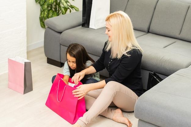 買い物をした後、家で楽しんでいる陽気な母と娘