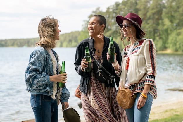 Веселые многонациональные девушки пьют пиво вместе на пляже, развлекаясь на базе отдыха