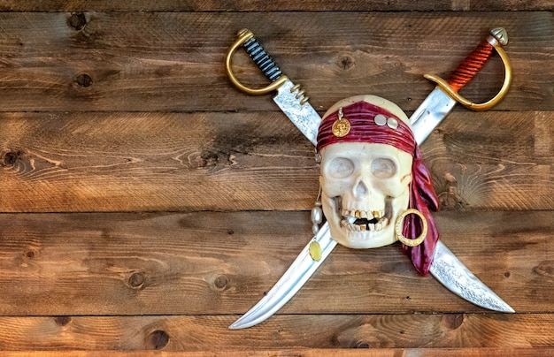 Jolly pirate scull in bandanna with crossed swords and golden teeth on wooden