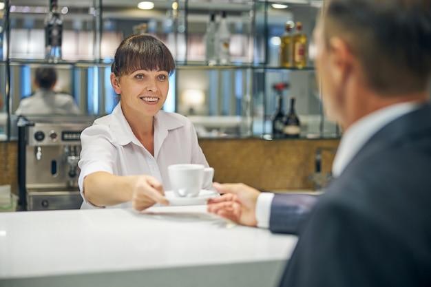 졸리 예쁜 여자가 공항 라운지 바에서 우아한 남자에게 커피 한 잔을 주고 있다