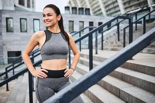 Jolly young female in sport outfit is standing after workout on stairs of urban building outdoors