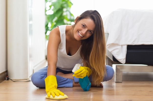 Jolly young maid cleaning floor with cloth